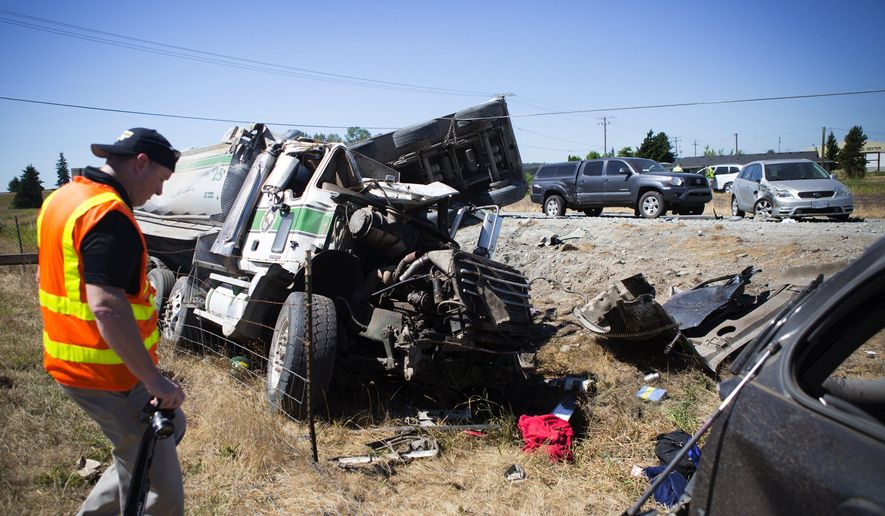 A Washington State Patrol photographer documents the scene after a large accident involving a truck carrying gravel Saturday, July 18, 2015, on Interstate 5 north of Seattle. Multiple people were injured in the crash and over a dozen vehicles were involved. (Lindsey Wasson/The Seattle Times via AP) SEATTLE OUT; USA TODAY OUT; MAGS OUT; TELEVISION OUT; NO SALES; MANDATORY CREDIT TO BOTH THE SEATTLE TIMES AND THE PHOTOGRAPHER