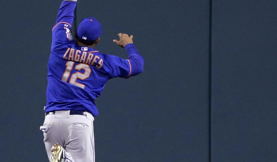 New York Mets center fielder Juan Lagares cannot reach a ball hit for an RBI-double by St. Louis Cardinals' Peter Bourjos during the eighth inning of a baseball game Friday, July 17, 2015, in St. Louis. The Cardinals won 3-2. (AP Photo/Jeff Roberson)