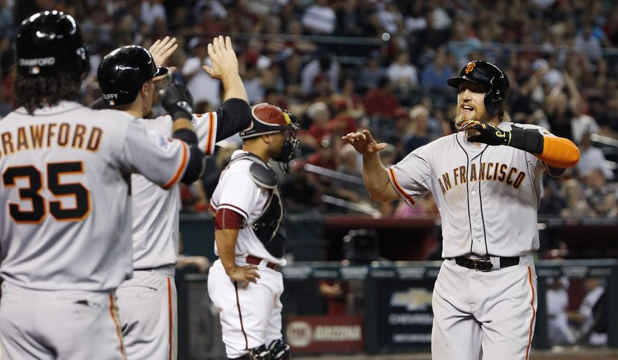San Francisco Giants' Hunter Pence, right, celebrates his two-run home run with teammates Brandon Crawford (35) and Matt Duffy, second from left, as Arizona Diamondbacks' Welington Castillo stands at home plate during the seventh inning of a baseball game Friday, July 17, 2015, in Phoenix. (AP Photo/Ross D. Franklin)