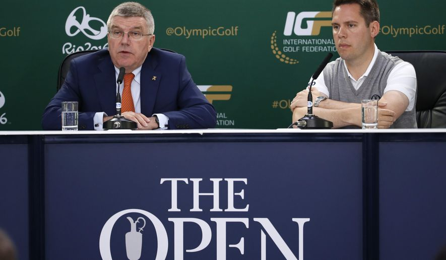 International Olympic Committee president Thomas Bach, left, speaks during a news conference during the second round of the British Open Golf Championship at the Old Course, St. Andrews, Scotland, Saturday, July 18, 2015. Golf will feature at the Rio 2016 Olympics. (AP Photo/Jon Super)