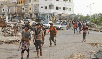 Fighters against Shiite rebels known as Houthis gather at a street in the port city of Aden, Yemen, Thursday, July 16, 2015. Saudi-backed Yemeni troops and fighters have driven Shiite rebels out of two major neighborhoods in the southern port city of Aden, Thursday, prompting street celebrations by residents after weeks of fierce fighting. (AP Photo/Abo Muhammed)