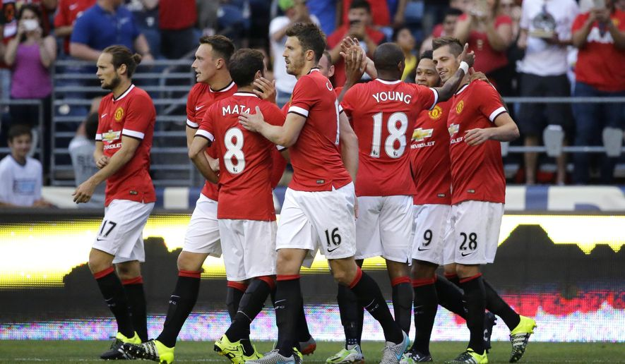 Manchester United's Morgan Schneiderlin (28), right, celebrates with teammates after he scored a goal against Club America during the first half of an international friendly soccer match, Friday, July 17, 2015, in Seattle. (AP Photo/Ted S. Warren)