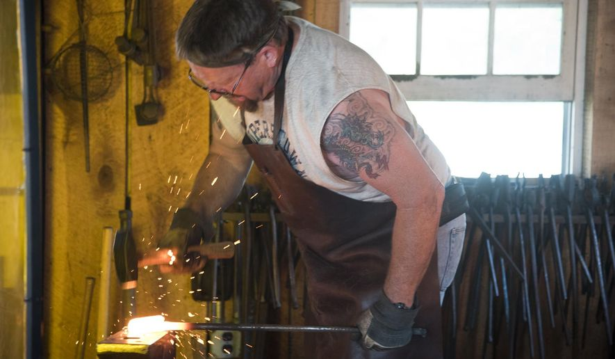 """ADVANCE FOR SATURDAY JULY 18 AND THEREAFTER - In a July 13, 2015 photo, Mark Ramey of Arnold heats a piece of hot iron at the forge at Kinder Farm Park in Annapolis, Md. Members of the Chesapeake Forge Blacksmith Guild gather at their """"clubhouse"""" at Kinder Farm Park, sweating over one of four 1,500 degree coal forges, and tinkering with their metal projects. (Joshua McKerrow/Capital Gazette via AP) MANDATORY CREDIT"""