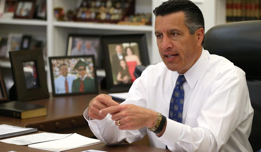 FILE - In this April 17, 2015, file photo, Nevada Gov. Brian Sandoval sits in his office at the Capitol in Carson City, Nev.  Sandoval is heading out on a trade mission to Europe including England, Ireland, Germany, Poland and Italy. (AP Photo/Cathleen Allison, File)