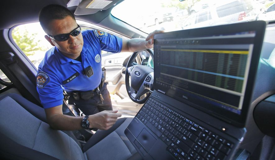 In this July 16, 2015, photo, Farmington Police Department district coordinator Martin Olsen talks about a new computer program that locks up a patrol car's computer screen when the vehicle reaches a certain speed at the Farmington Police Department in Farmington, N.M. (Jon Austria/The Daily Times via AP) MANDATORY CREDIT