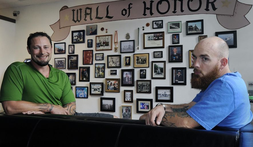 In this July 8, 2015, photo, with a wall of honor filled with personal photos of service men and women displayed prominently next to their of their Olympia office space veterans Dante Cammarata, left, and Andrew Collins pose for a photo in Olympia, Wash. Collins has launched a support group called Twenty22Many, which is focused on reducing suicide rates among military veterans with help from medical marijuana. (Steve Bloom/The Olympian via AP)