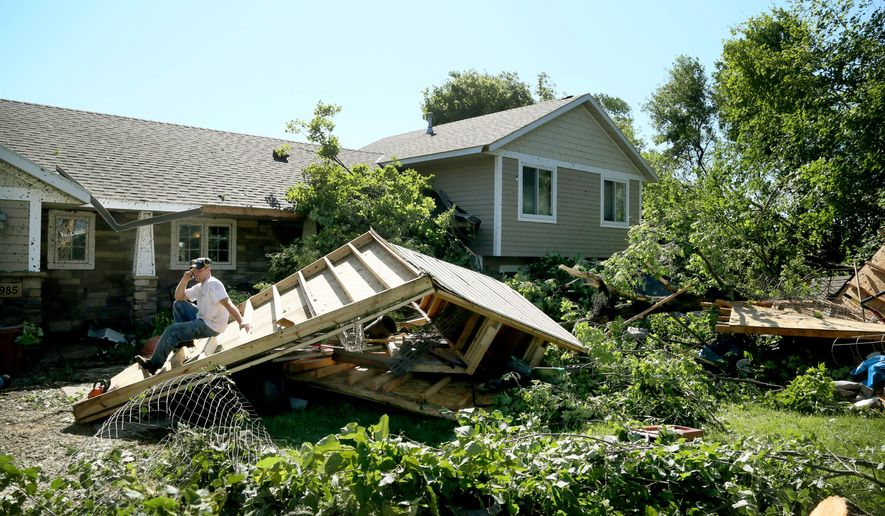 Jason Bogema sits atop a destroyed building on his property in Hollywood Township, where an EF1 tornado with 105 mph winds touched down Saturday, July 18, 2015, near Watertown, Minn. An EF1 tornado touched down near Watertown west of the Twin Cities overnight, damaging buildings and flipping cars but caused no injuries, the National Weather Service said Saturday. (David Joles/Star Tribune via AP)  MANDATORY CREDIT; ST. PAUL PIONEER PRESS OUT; MAGS OUT; TWIN CITIES LOCAL TELEVISION OUT