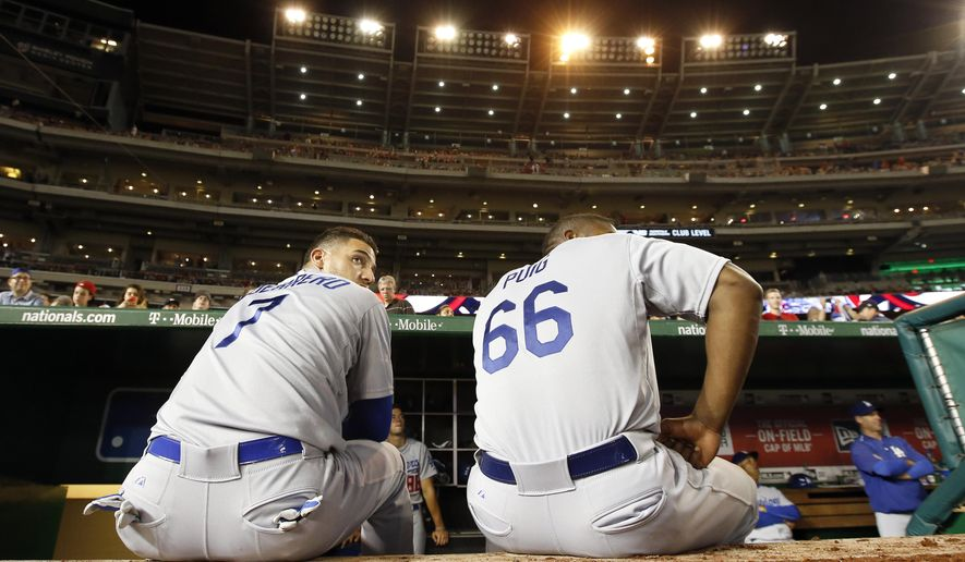Los Angeles Dodgers' Alex Guerrero (7) and right fielder Yasiel Puig (66) sit on the edge of the dugout under the lights that are out, as play was halted for the second time, during the fifth inning of a baseball game against the Washington Nationals at Nationals Park, Friday, July 17, 2015, in Washington. (AP Photo/Alex Brandon)