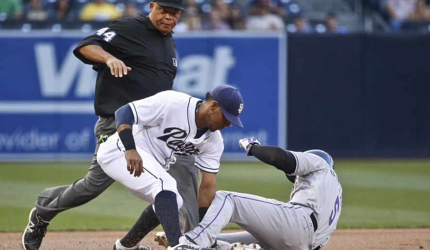 San Diego Padres third baseman Yangervis Solarte puts the tag on Colorado Rockies' Carlos Gonzalez who is out trying to advance from second on an infield ground ball during the first inning of a baseball game Friday, July 17, 2015, in San Diego. The umpire is Kerwin Danley. (AP Photo/Lenny Ignelzi)