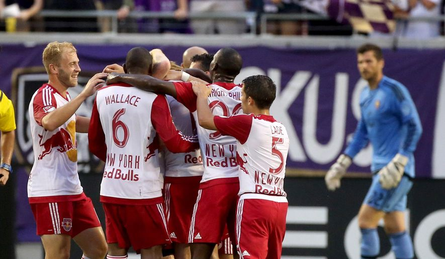 New York Red Bull players celebrate their first goal of the game as Orlando's goalkeeper Tally Hall watches, right, during an MLS soccer match, Saturday, July 18, 2015 in Orlando, Fla. (Joe Burbank/Orlando Sentinel via AP) MAGS OUT; NO SALES; MANDATORY CREDIT