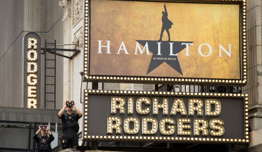 Secret Service officers stand on the awning of the Richard Rodgers Theatre in New York, Saturday, July 18, 2015, as President Barack Obama, daughters Sasha and Malia, his sister Maya Soetoro-Ng, her husband Konrad Ng, and friends attend a performance of Hamilton. (AP Photo/Andrew Harnik)