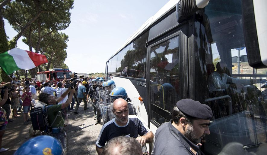 Residents and far right demonstrators protest as a bus carrying migrants arrives to house asylum seekers in a former school in Rome, Friday, July 17, 2015. (Massimo Percossi/ANSA via AP)