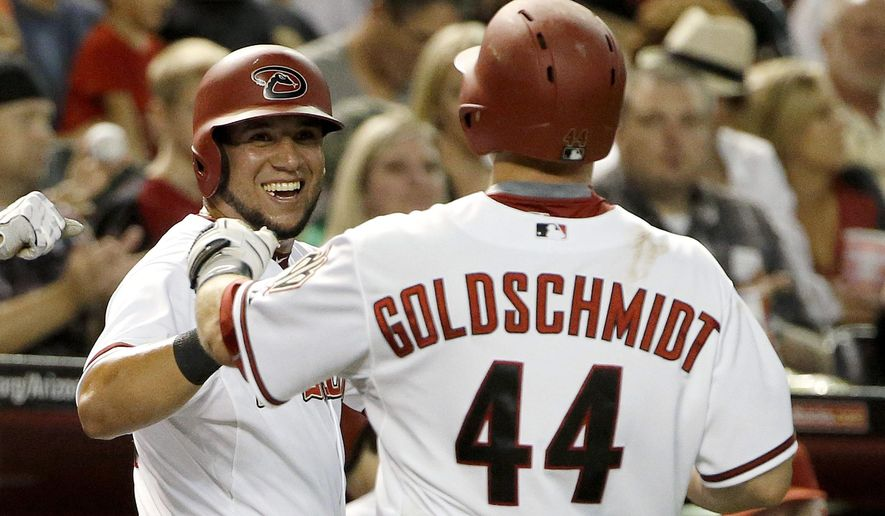 Arizona Diamondbacks' David Peralta, left, smiles after scoring a run against the San Francisco Giants on a sacrifice fly by Arizona Diamondbacks' Paul Goldschmidt (44) during the third inning of a baseball game Friday, July 17, 2015, in Phoenix. (AP Photo/Ross D. Franklin)