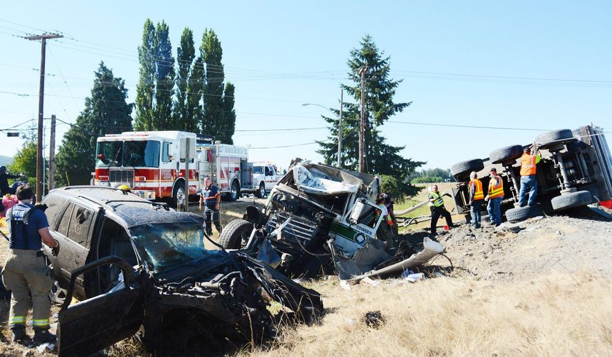 Authorities investigate the scene of an accident involving a tractor-trailer hauling gravel Saturday, July 18, 2015, in Mount Vernon, Wash. Multiple people were injured in a crash involving over a dozen vehicles on Interstate 5 north of Seattle. (Brandy Shreve/The Skagit Valley Herald via AP) MANDATORY CREDIT