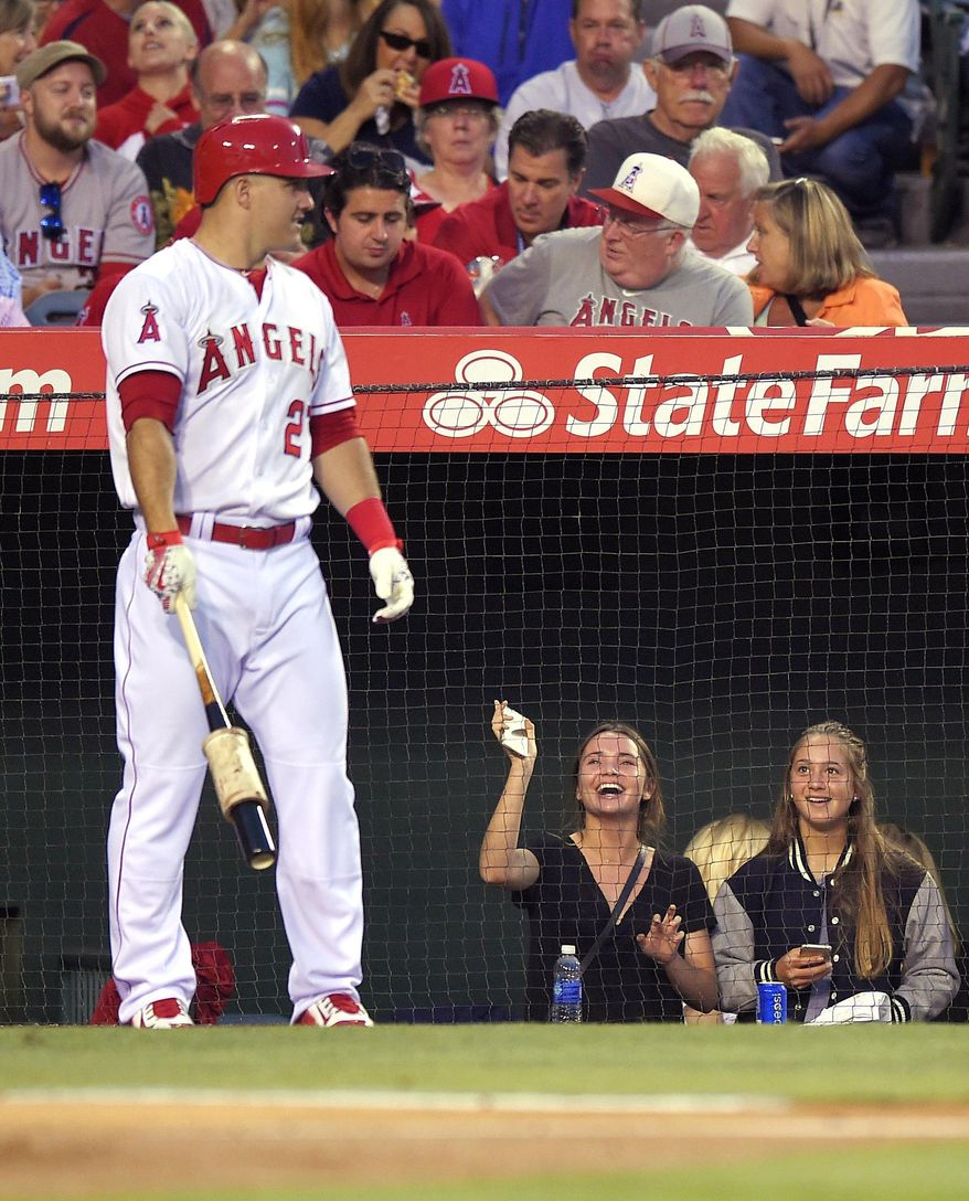 Fans try to get the attention of Los Angeles Angels' Mike Trout as he gets ready to bat during the fourth inning of a baseball game against the Boston Red Sox, Friday, July 17, 2015, in Anaheim, Calif. (AP Photo/Mark J. Terrill)
