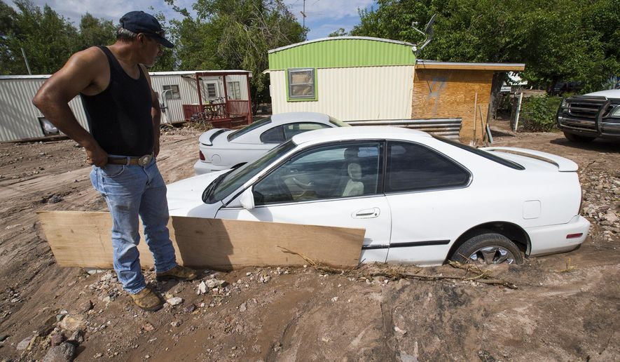 Tim Guzman looks at two of his cars stuck in mud at the Aztec Village RV and Mobile Home Park in Wickenburg, Ariz., Sunday July 19, 2015. The National Weather Service says between 1 and 4 inches of rain fell in and around Wickenburg Saturday afternoon in a 90-minute period. (Michael Chow/The Arizona Republic via AP)  MARICOPA COUNTY OUT; MAGS OUT; NO SALES; MANDATORY CREDIT