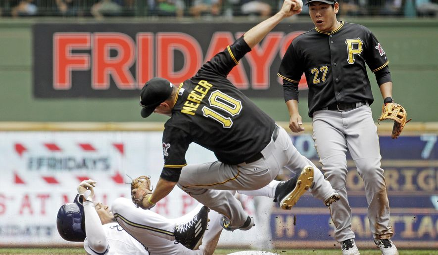 Pittsburgh Pirates' Jung Ho Kang (27) watches as teammate Jordy Mercer (10) collides with Milwaukee Brewers' Carlos Gomez during the second inning of a baseball game Sunday, July 19, 2015, in Milwaukee. Gomez was out on the play and Mercer left the game on a cart. (AP Photo/Morry Gash)
