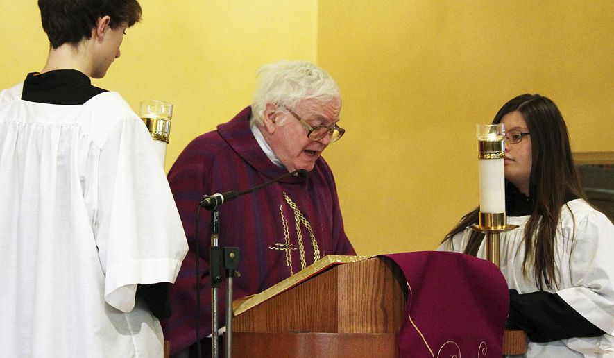 In this March 15, 2015 photo, Father John Doyle reads the Gospel at St. Ambrose Church in Crest Hill, Ill. Doyle retired on June 7, 2015 and although he has retired from parish work, he is not planning to retire from ministry.  (Christine Johnson/The Herald-News via AP)  CHICAGO TRIBUNE OUT, MANDATORY CREDIT