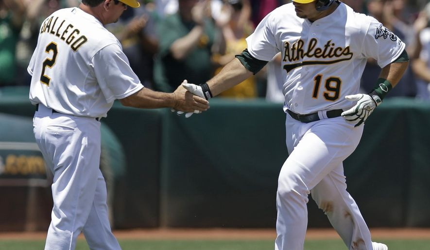 Oakland Athletics' Josh Phegley, right, is congratulated by third base coach Mike Gallego (2) after hitting a two-run home run off Minnesota Twins' Tommy Milone in the second inning of a baseball game Sunday, July 19, 2015, in Oakland, Calif. (AP Photo/Ben Margot)