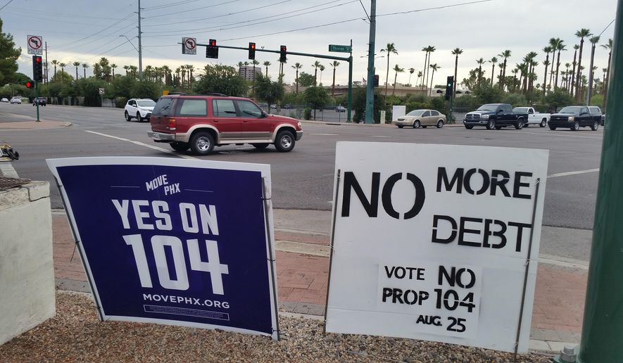 This Saturday, July 18, 2015 photo shows campaign signs for, left, and against an initiative to expand Phoenix's transportation systems at an intersection in Phoenix. With city elections in Phoenix next month and 2016 races around the corner, Arizona regulators are warning people that they might need to pull up stakes on the many campaign signs on lawns and street corners. (AP Photo/Terry Tang)