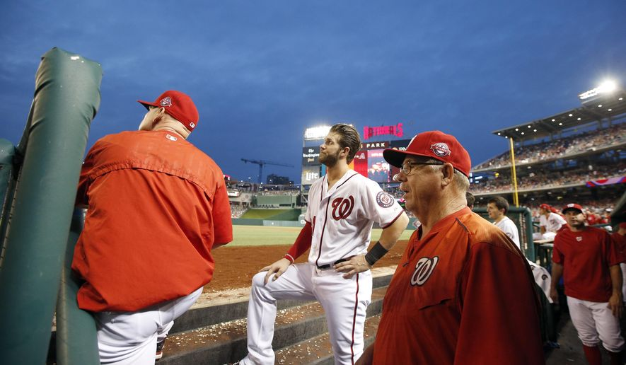 Washington Nationals manager Matt Williams, left, Bryce Harper (34) and pitching coach Steve McCatty look up at the lights that went out after play was halted during the fourth inning of a baseball game against the Los Angeles Dodgers at Nationals Park, Friday, July 17, 2015, in Washington. (AP Photo/Alex Brandon)