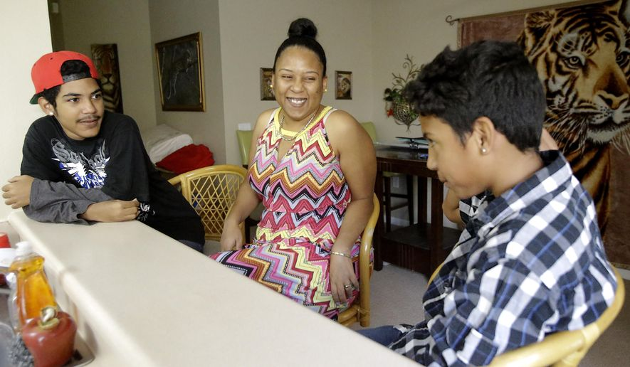 In this Thursday, July 16, 2015 photo, Mayra Rios, center, talks with her sons, Abdiel, 13, right, and Jonatan, 15, at their home in Orlando, Fla. Rios recently left her native Puerto Rico because of constant bullying her autistic son faced at school and the lack of services available for him. As Puerto Rico struggles with an unpayable debt, an unemployment rate over 12 percent, rising violence and a stagnant economy that offers little opportunity to thrive, thousands of its residents are abandoning the island for central Florida. (AP Photo/John Raoux)