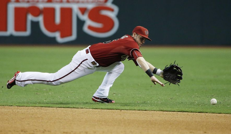 Arizona Diamondbacks' Chris Owings dives in vain for a grounder hit by San Francisco Giants' Joe Panik for a single during the eighth inning of a baseball game Sunday, July 19, 2015, in Phoenix.  The Giants defeated the Diamondbacks 2-1. (AP Photo/Ross D. Franklin)