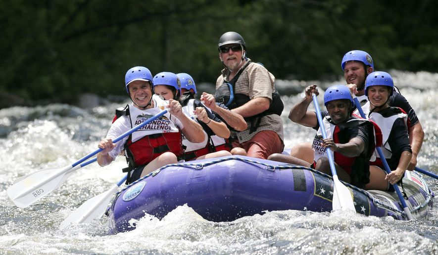 New York Gov. Andrew Cuomo, left, Counsel to the Governor Alphonso David, right, and their team compete in a rafting competition during the Adirondack Challenge on the Indian River on Sunday, July 19, 2015, in Indian Lake, N.Y. (AP Photo/Mike Groll)
