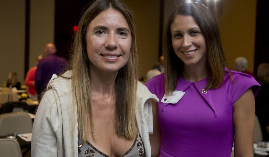 Giedre Cohen, 37, of Calabasas, Calif., and Carrie Richardson, 34, of Montgomery, Ala., pose for a picture during a break at the Alzheimer's Association International Conference in Washington, Saturday, July 18, 2015. Saturday for the first time, researchers brought together dozens of these families with the very rarest form of Alzheimer's, young and inherited--patients, patients-to-be and their healthy loved ones _ from as far as Australia and Britain to meet face-to-face.  (AP Photo/Manuel Balce Ceneta)