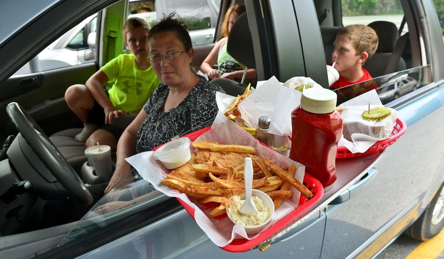 ADVANCE FOR MONDAY JULY 20 AND THEREAFTER - In this Tuesday June 23, 2015 photo, Miranda Huffman of Lewisburg and her three children Koltyn, 7, Keiley, 8 and Kaiden, 10, all enjoy the fare at Jim's Drive-In in Lewisburg, W.Va. Massie bought the restaurant in 2001 after working as a waitress at Jim's Drive-In in 1969. Her 1969 paystub now hangs on the wall.  (Bob Wojcieszak/Daily Mail via AP)