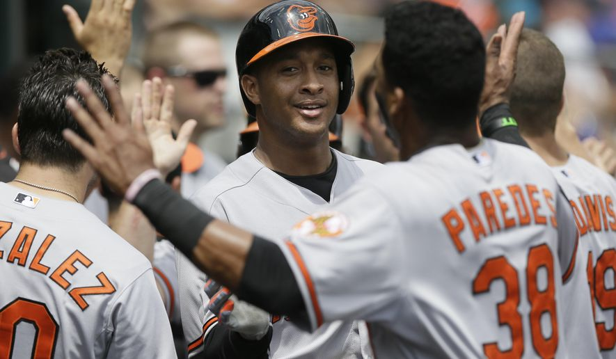 Baltimore Orioles' Jonathan Schoop, center, celebrates his three-run home run with teammate Jimmy Paredes (38) during the fourth inning of a baseball game against the Detroit Tigers, Sunday, July 19, 2015, in Detroit. (AP Photo/Carlos Osorio)