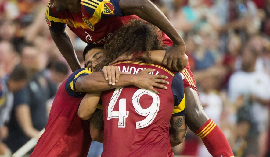 Real Salt Lake players celebrate a goal by midfielder Javier Morales, obscured, during  the first half of an MLS soccer game against the Houston Dynamo, Saturday, July 18, 2015, in Sandy, Utah. (Rick Egan/The Salt Lake Tribune via AP)