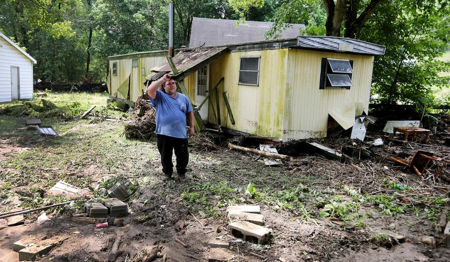 Jeff Downing, walks around his property in Ripley, Ohio, Sunday, July 19, 2015. Downing's mobile home had previously been in the foreground where the bricks are prior to a late evening flash flood. The flood swept away a mobile home late Saturday, killing three members of a family of six huddling for safety inside, authorities said. (Liz Dufour/The Cincinnati Enquirer via AP)  MANDATORY CREDIT;  NO SALES