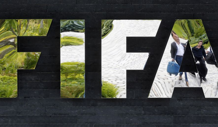 FILE - In this May 27, 2015, file photo, two persons are reflected in the FIFA logo at the FIFA headquarters in Zurich, Switzerland. Swiss authorities said Thursday, July 16, 2015, that one of the seven FIFA officials arrested in Zurich as part of a U.S. corruption probe was extradited to the United States they day before. Switzerland's Federal Office of Justice didn't identify the FIFA official.  (AP Photo/Michael Probst, File)