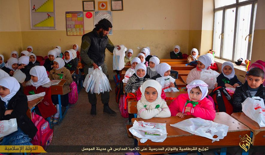 An Islamic State militant distributes plastic bags full of stationery and other gifts to young students at a school in Mosul, northern Iraq. (Associated Press)