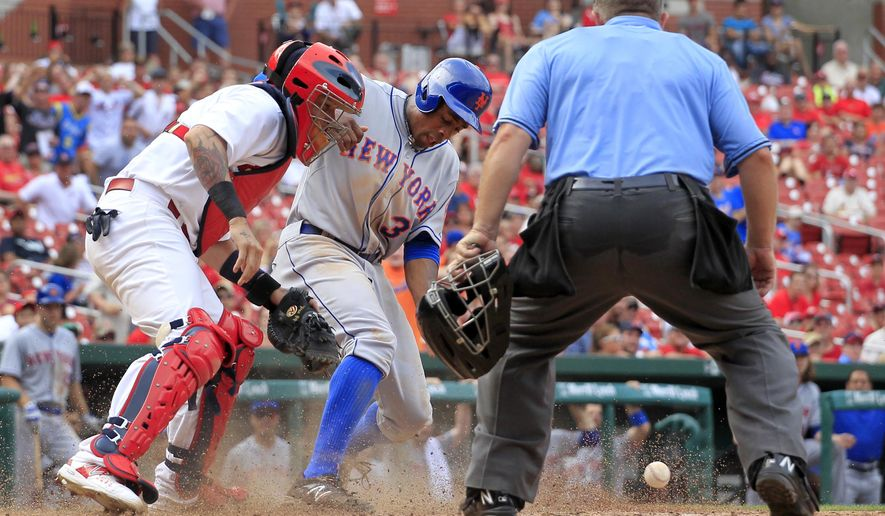 New York Mets' Curtis Granderson, center, scores as the throw gets away from St. Louis Cardinals catcher Yadier Molina, right, and home plate umpire Greg Gibson watches during the 13th inning of a baseball game Sunday, July 19, 2015, in St. Louis. (AP Photo/Jeff Roberson)