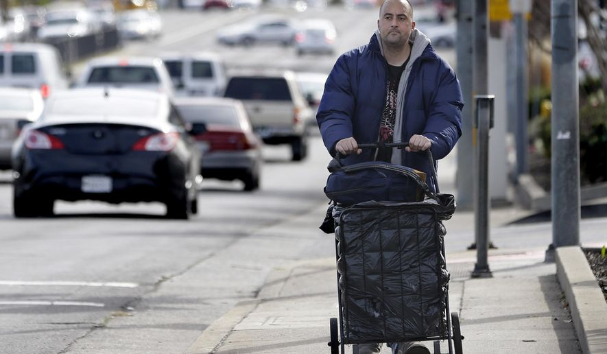 FILE - In this Feb. 11, 2015 file photo, Medi-Cal patient Richard Olivares, pushes his cart of belongings along a street in Sacramento Calif. California has enrolled 2.3 million people, nearly three times more than anticipated, under an optional expansion of the state's medicaid program. Coupled with higher than expected enrollment, Medi-Cal  is now putting financial pressure on the state that was quick to embrace President Barack Obama's health care initiative.(AP Photo/Rich Pedroncelli, File)