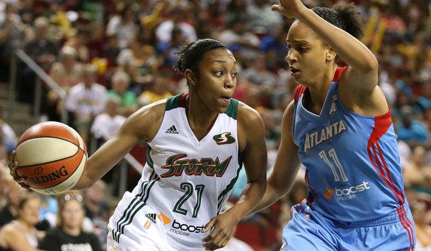 Seattle Torm's Renee Montgomery, left, brings the ball around Atlanta Dream's Cierra Burdick during a WNBA basketball game in Seattle, Saturday, July 18, 2015. (Sy Bean/The Seattle Times via AP) SEATTLE OUT; USA TODAY OUT; MAGAZINES OUT; TELEVISION OUT; NO SALES; MANDATORY CREDIT TO BOTH THE SEATTLE TIMES AND THE PHOTOGRAPHER
