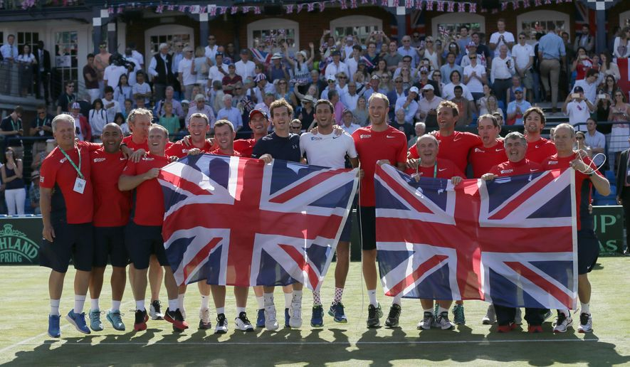 Britain's Andy Murray, centre left, celebrates with his teammates after beating France's Gilles Simon, taking Britain to the semifinal stage, winning the quarterfinal tennis matches of the Davis Cup at the Queen's Club in London, Sunday July 19, 2015. (AP Photo/Tim Ireland)