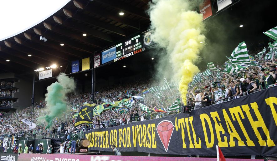 Portland Timbers fans celebrate a goal with colored smoke during the first half of an MLS soccer game against the Vancouver Whitecaps in Portland, Ore., Saturday, July 18, 2015. (AP Photo/Don Ryan)