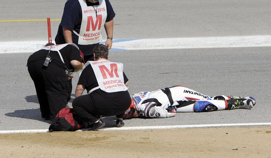 In this Sunday, July 19, 2015, photo, medical and track personnel attend to Spanish rider Bernat Martinez after a chain reaction crash on the first lap of a World Superbike race at Mazda Raceway at Laguna Seca in Monterey, Calif. Two Spanish racers were killed in the crash. Race organizers MotoAmerica identified the dead as 35-year-old Bernat Martinez and 27-year-old Daniel Rivas Fernandez. Both were taken to hospitals, where they later died.  (Nic Coury/Monterey County Weekly via AP) MANDATORY CREDIT FOR PAPER AND PHOTOGRAPHER. MONTEREY HERALD OUT , SALINAS CALIFORNIAN OUT , SANTA CRUZ SENTINEL OUT , SAN JOSE MERCURY OUT , LOCAL TV OUT