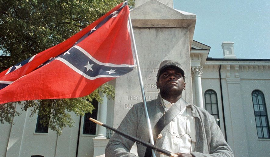 In this May 8, 2000, file photograph, Anthony Hervey holds a Confederate flag while standing underneath the Confederate monument in Oxford, Miss. The Highway Patrol says 49-year-old Hervey was killed Sunday, July 19, 2015, when his 2005 Ford Explorer left the roadway and overturned on Mississippi Highway 6 in Lafayette County. (Bruce Newman/The Oxford Eagle via AP, File)