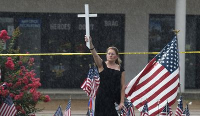 Lisa Camp holds a cross in the rain near the Armed Forces Career Center on Lee Highway, Sunday, July 19, 2015, in Chattanooga, Tenn. Muhammad Youssef Abdulazeez attacked two military facilities, including the career center, last week in a shooting rampage that killed a U.S. Navy sailor and four Marines. (John Rawlston/Chattanooga Times Free Press via AP)