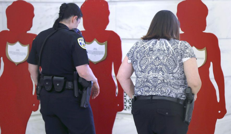 Sherwood Police Lt. Jamie Michaels, left, and Detective Heather Meadows read accounts of domestic violence placed on painted cutouts after a news conference at the Arkansas state Capitol in Little Rock, Ark., Monday, July 20, 2015. Arkansas lawmakers Monday said measures approved by the Legislature earlier this year are aimed at preventing domestic violence and helping victims. (AP Photo/Danny Johnston)