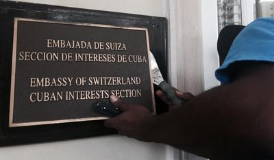A worker the removes Cuban Interests Section sign in Washington on July 15, just days prior to the building being accredited as the Cuban Embassy. (Associated Press)