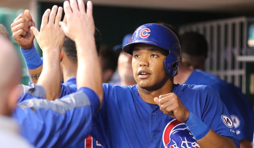 Chicago Cubs second baseman Addison Russell is congratulated by teammates after scoring on a hit by Kris Bryant during the fifth inning of a baseball game against the Cincinnati Reds, Monday, July 20, 2015, in Cincinnati. (AP Photo/Gary Landers)