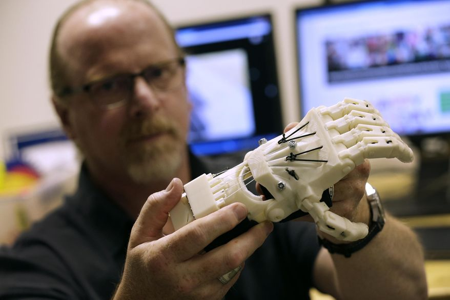 Mechanical Design instructor Jeff Laurich holds a 3D designed prosthetic hand Wednesday, July 15, 2015, Fox Valley Technical College in Grand Chute, Wis. Laurich and students are participating in the gloabal e-NABLE program. (Dan Powers/Post-Crescent Media via AP)