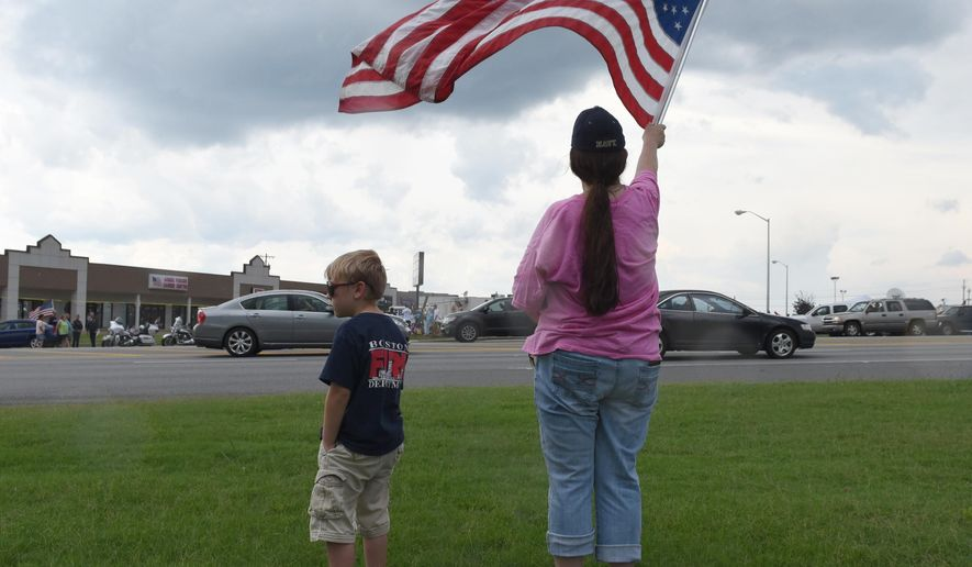 Cheryl Jenkins waves an American flag next to Zachary Meadows across from the Armed Forces Career Center on Lee Highway, Sunday, July 19, 2015, in Chattanooga, Tenn. Muhammad Youssef Abdulazeez attacked two military facilities, including the career center, last week in a shooting rampage that killed a U.S. Navy sailor and four Marines. (John Rawlston/Chattanooga Times Free Press via AP)