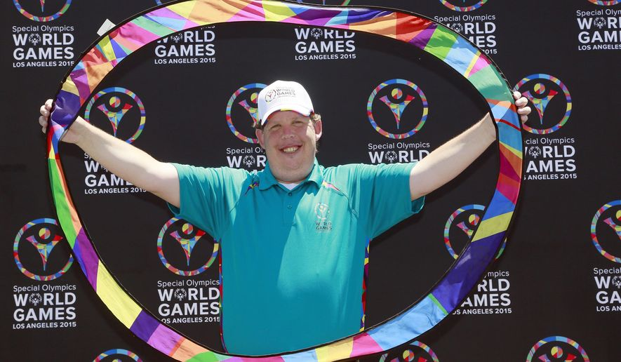 In this Thursday, July 16, 2015, photo, former Special Olympics athlete and coach Dustin Plunkett poses with the Special Olympics' Circle of Inclusion in Carson, Calif. Plunkett is helping organize this year Special Olympics World Games in Los Angeles, which will feature thousands of athletes from over 100 countries competing in more than two dozen sports when it begins next week. (AP Photo/Nick Ut)