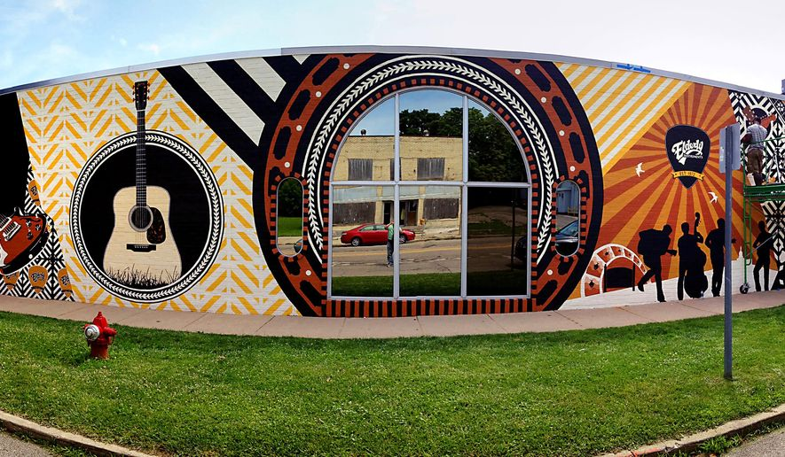 "A panoramic picture as designer Jennifer Springman and Ndadaye Merchior work and are close to completing the new 68-foot-long mural outside Elderly Instruments in Lansing's Old Town Thursday July 16,  2015.  Springman, the niece of Elderly Instruments owner Stan Werbin, designed the custom mural to reflect the many aspects of music and instruments at Elderly, along with Lansing.  The Martin Guitars ""herringbone"" ornamentation is featured prominently, and the public is invited to the  mural grand unveiling on Tuesday, July 21. (Rod Sanford/Lansing State Journal via AP) MANDATORY CREDIT NO SALES"